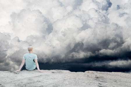 Man Sitting Alone High on a Hill Reaching Clouds