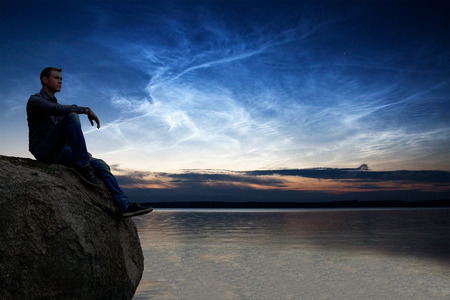Man Sitting on a Cliff Watching Noctilucent Clouds over Lake