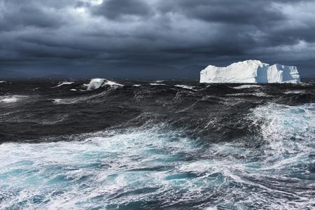 폭풍우가 치는 대양에서 표류하는 큰 빙산 스톡 콘텐츠