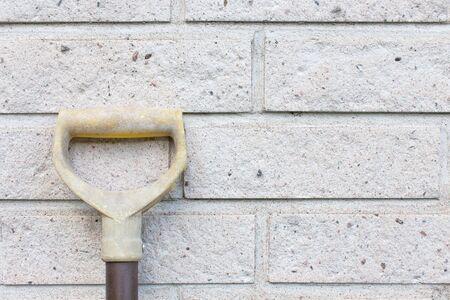 Shovel Resting Against Brick Wall