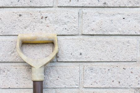 Shovel Resting Against Brick Wall
