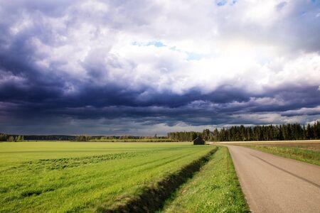 Rural Road Leading Forward Towards Dark Moody Clouds