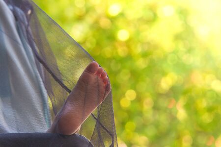 Baby Taking Nap Outside in Stroller with Cute Small Leg Peeking Out Under Mosquito Net.