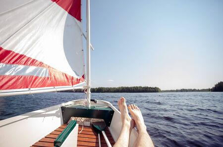 Sailing Relaxed with Small Sailing Boat Laying Feet on Board Zdjęcie Seryjne