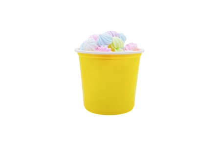 Colorful meringues in yellow plastic cup isolated on white background. Zdjęcie Seryjne