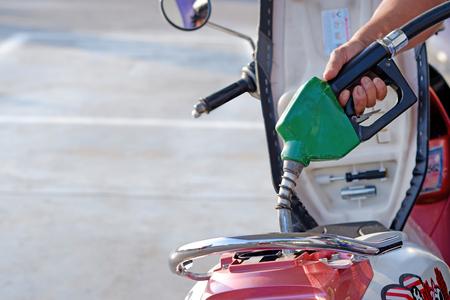 燃料ディスペンサーガソホル91、ガソリンピストルポンプのためのオイルディーゼル自動ノズルを保持するクローズアップハンド。