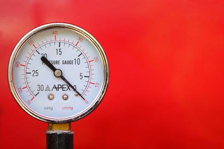 Chiudere il manometro dell'acqua su sfondo rosso.