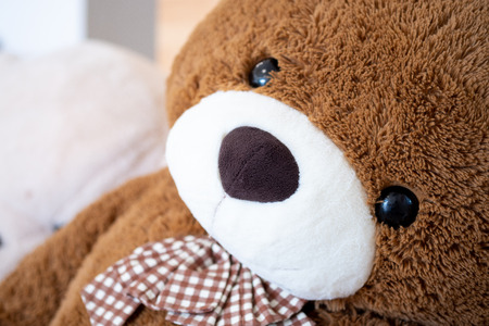 Teddy bear doll resting comfortably on soft focus background and vintage color tone. Close up Big doll Cute smiling friendly. Banque d'images