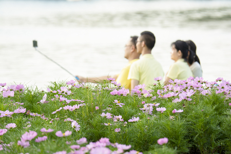 Happy family Sit back and relax living Eating a picnic Happy selfies take family photos. In the midst of flowers and ponds in the middle of a Suan Luang Rama IX park in Thailand