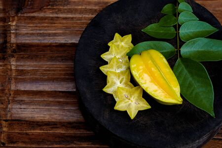 Star apple (Carambola, starfruit, Ma fueng, Golden Star, Newcomb, Golden star) on a round wooden cutting board. Slice ripe the fruit into pieces beautifully placed on wooden containers. top view