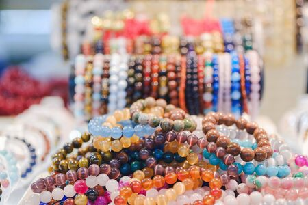 Various beautiful gem bracelets stacked together for sale in the market.