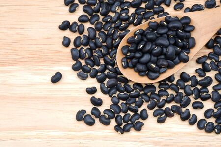 Close-up Raw black beans in a wooden spoon on wooden background, top view.