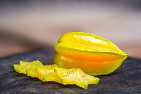 Star apple (Carambola, starfruit, Ma fueng, Golden Star, Newcomb, Golden star) on wooden background. Slice ripe the fruit into pieces beautifully placed on wooden containers. Clipping path.