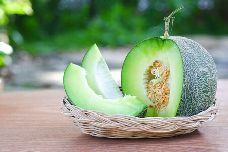 Bright green melon is placed on a White wicker basket on a blurred garden background. Sliced of Honeydew melons Fruits or healthcare concept.Selective focus.