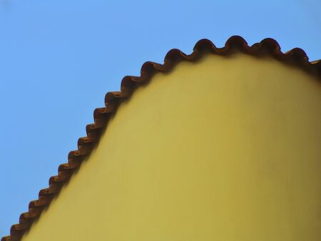 Part of a rooftop and yellow side of a house against the blue sky photo