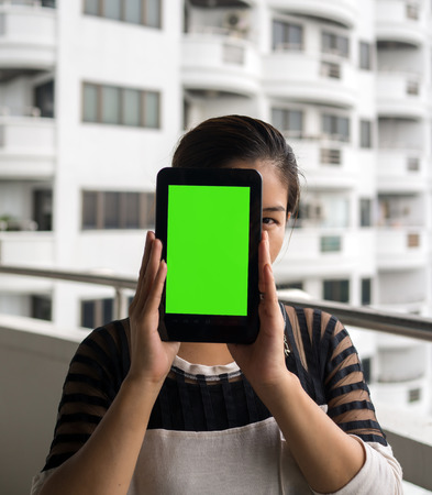 eye pad: Asian woman holding tablet in her hands in front of her face with blank green screen and white building in the background.