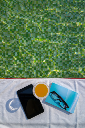 Tablet with empty screen, a glass of orange juice and blue book with glasses on the white towel next to the swimming pool with ripples and green mosaic tile bottom. photo
