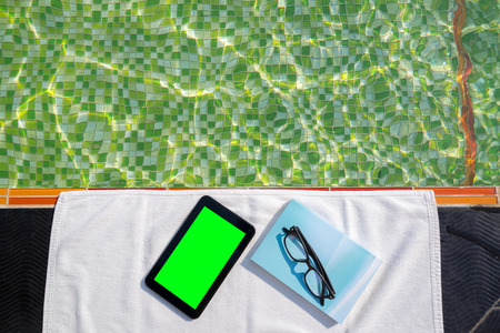 Tablet with blank green screen and blue book with glasses lying on white towel next to the pool with ripples and green mosaic tiles. photo