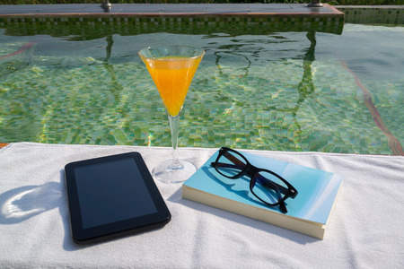 Tablet with empty screen, a glass of orange juice and blue book with glasses on the white towel next to the swimming pool with ripples and green mosaic tile bottom.