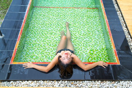 Asian girl in black bikinis lying in the swimming pool with green mosaic tile. photo
