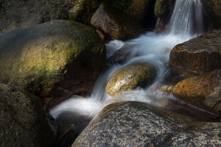 large rocks: Clear water flowing and falling around the large rocks. Stock Photo