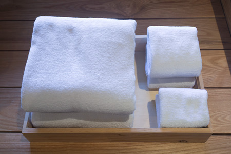 Different sizes of folded white towels in a wooden tray.