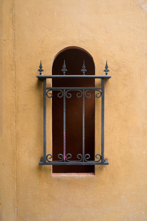 iron barred: Black iron bar covering long curved window on bright brown cement wall.