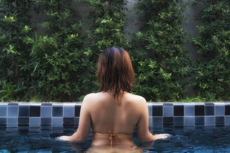 sexy female body: Asian girl with short hair in golden bikini standing in blue private pool in the garden.