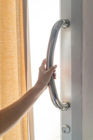 cerrar la puerta: sostenedor de Asia mujer explotación de la mano de cristal de acero de la puerta con cortina crema.