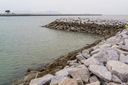 seawall: Long stone seawall in the sea.