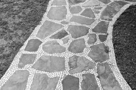 Texture of cobblestone and pebbles walkway in black and white.