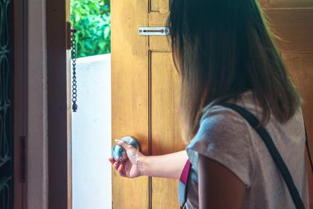아시아 여자 잡아 문 손잡이 개방 갈색 나무로되는 문. 스톡 콘텐츠
