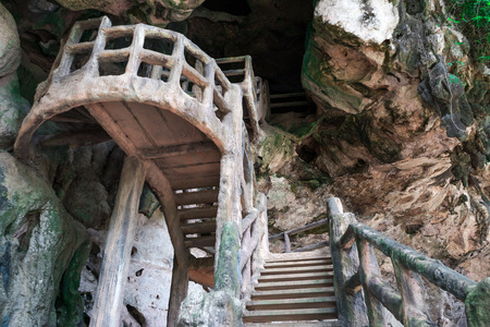 dark cave: Man made stairs upto the dark cave on rocky cliff. Stock Photo