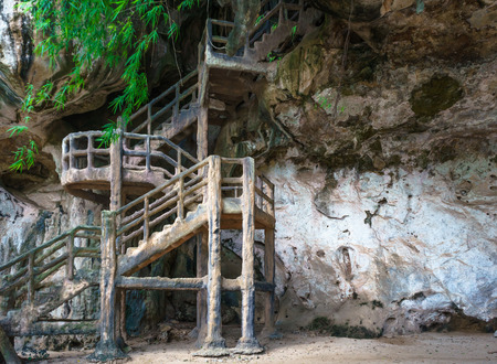 man made: Man made stairs upto the dark cave on rocky cliff. Stock Photo