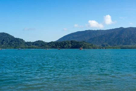 Small bamboo raft houses in the sea with green mountain and blue sky background. Stock Photo