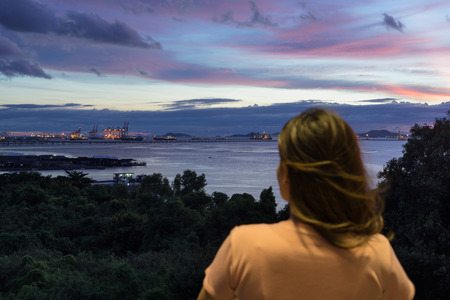 Asian woman looking at Laem Chabang Port view in Chonburi, Thailand at night. Stock Photo
