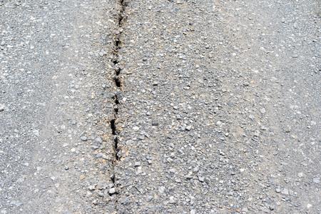 Deep crack on old damaged asphalt road.