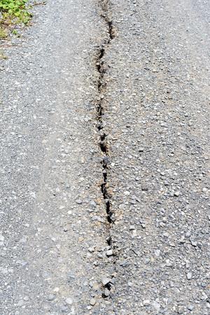Long deep crack on old damaged asphalt road.