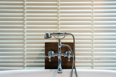 Steel faucets and shower head on wooden board with white wooden chick curtain background. Stock Photo