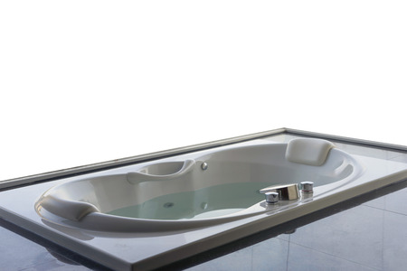 Empty white massaging jetted bathtub with blank white window background.