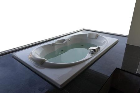 Empty white ceramic massaging jetted bathtub with blank white background.