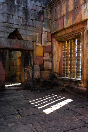 Ancient sandstone sanctuary with old stone floor and wall with window light and shadow.