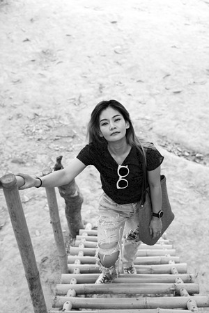 Black and white image of Asian woman standing on bamboo stairs in rural Thailand.
