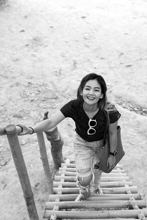 Asian woman smiling standing on bamboo stairs in black and white.