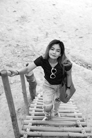 Black and white image of Asian woman smiling standing on bamboo stairs.