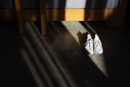 White running shoes on concrete floor in dark room with light and shadow.