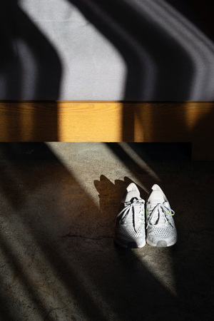 Running shoes in dark room with light and shadow on wooden sofa.