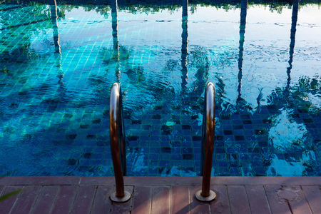 Reflection of palm trees and sky on blue swimming pool with steel ladder.