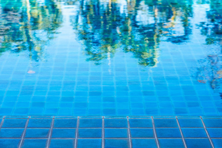 Abstract of green trees reflection on swimming pool with blue mosaic tiles. 版權商用圖片