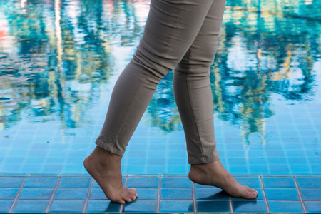 Female legs with brown pants walking on the poolside with trees reflection on the swimming pool.